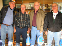 Four Retirees with Frozen Turkeys by Trophy Case