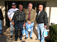 Three Retirees with Frozen Turkeys Outside Doorway